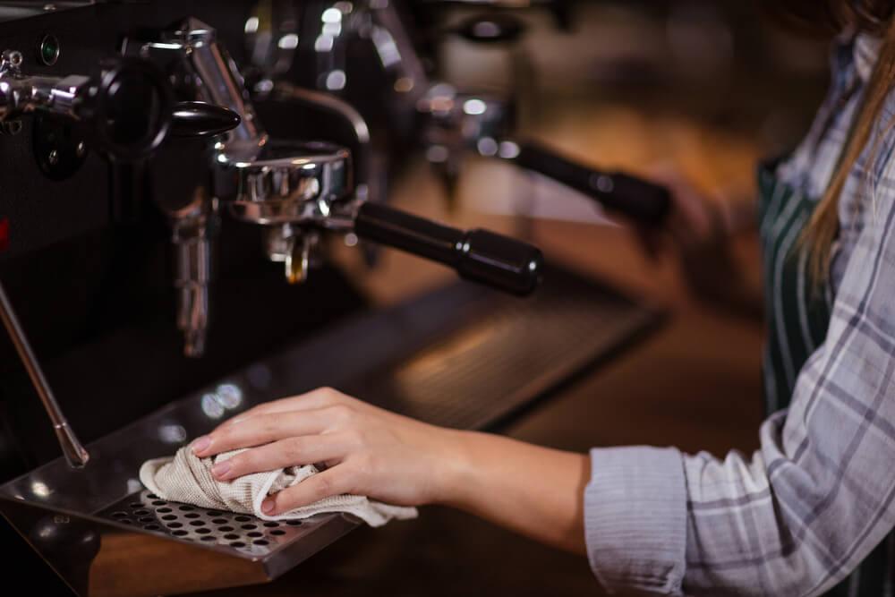 kobieta myje ściereczką ekspres do kawy