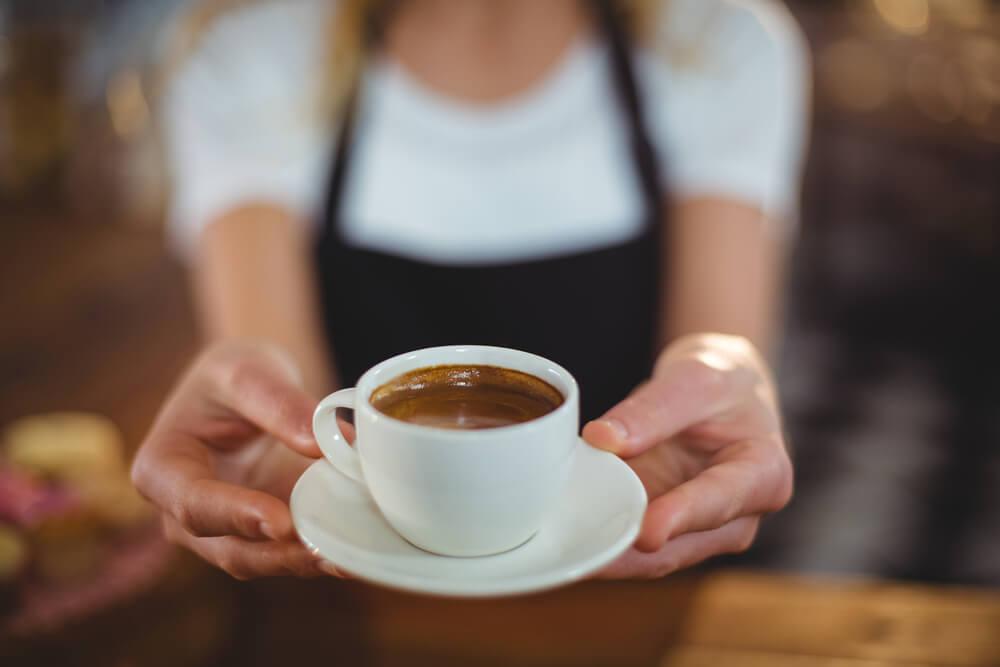 kobieta podające filiżankę kawy